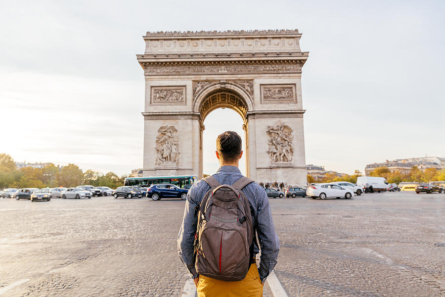 Tourist with backpack walking towards Arc de Triomphe in Paris, France Photograph by Alexander Spatari