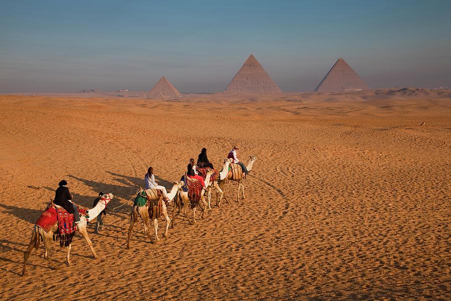 Tourists On Camels & Pyramids Of Giza Photograph by Richard Ianson