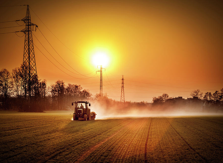 Tractor In A Field At Sunset Photograph by Rinocdz