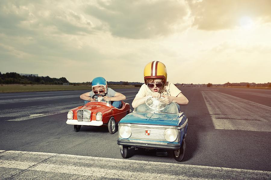 Two boys in pedal cars crossing finishing line on race track Photograph by Westend61