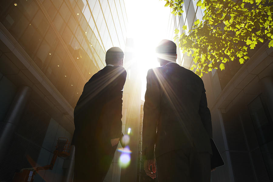 Two businessmen looking up into the sun. Photograph by Ezra Bailey
