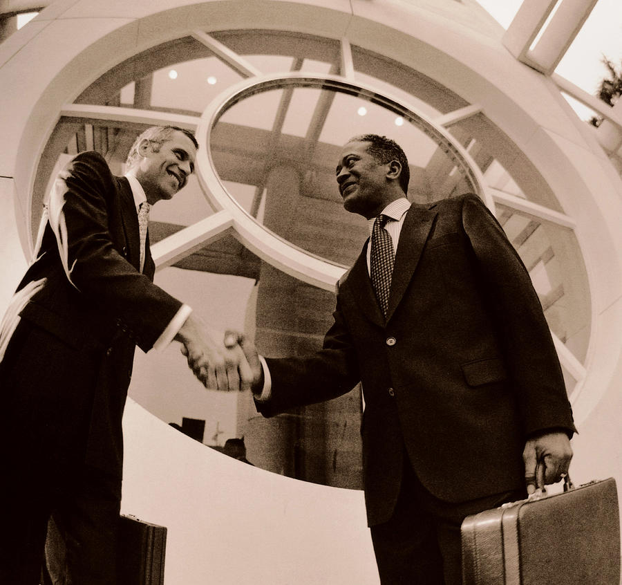 Two Businessmen Shaking Hands, Low Angle View (toned B&w) by Getty Images