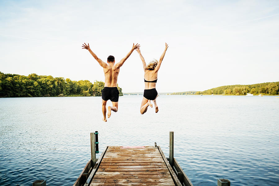 Two Friends Jumping Off Jetty At Lake Together Photograph by TommL