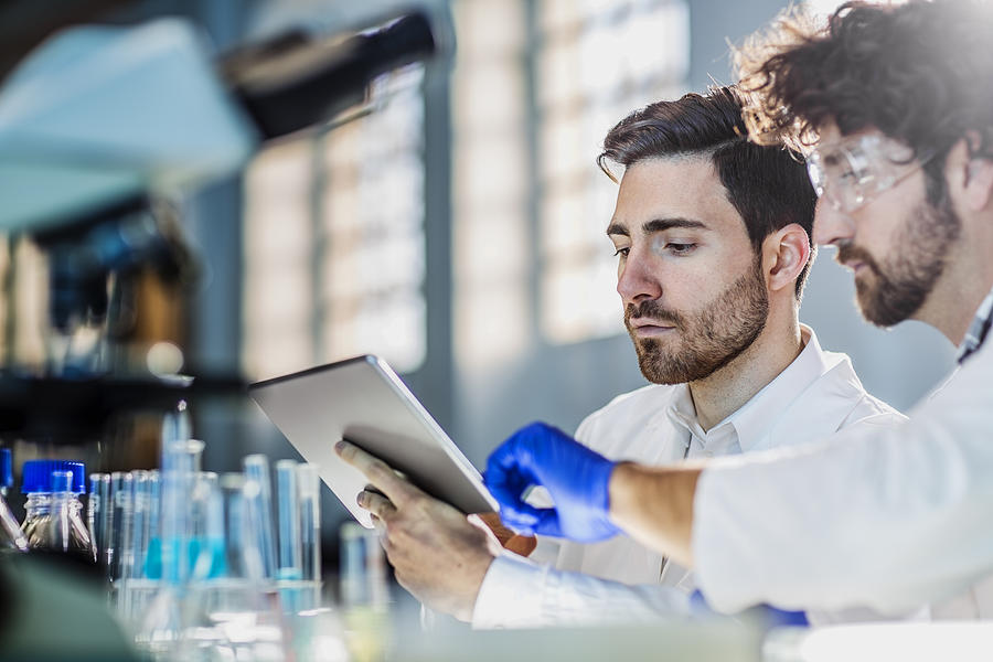 Two Scientist Using Digital Tablet In Laboratory Photograph by Poba