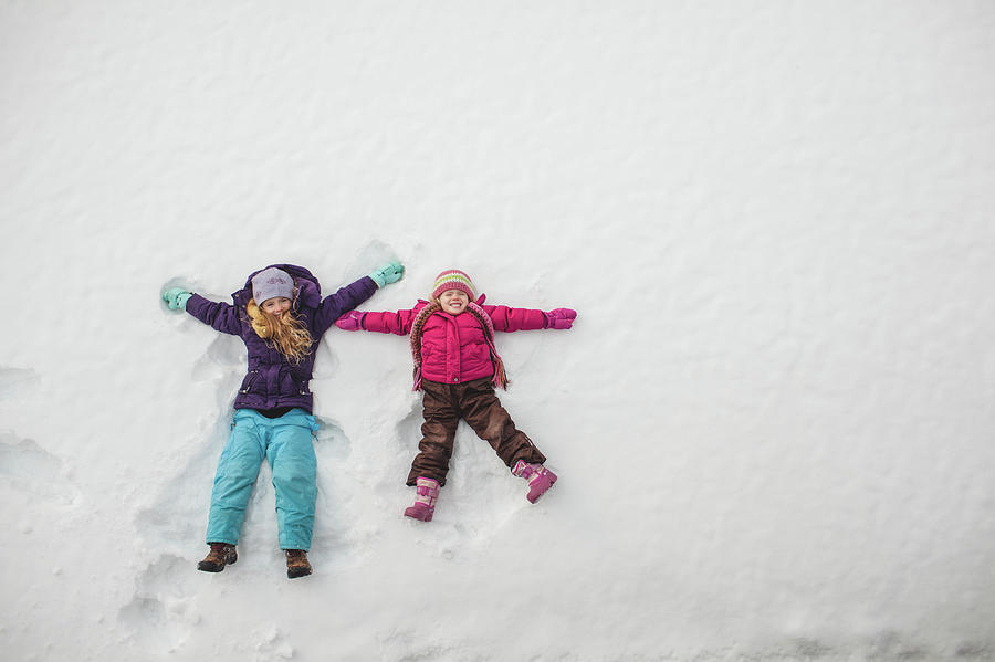Two Sisters Playing, Making Snow Angels Photograph by Hugh Whitaker