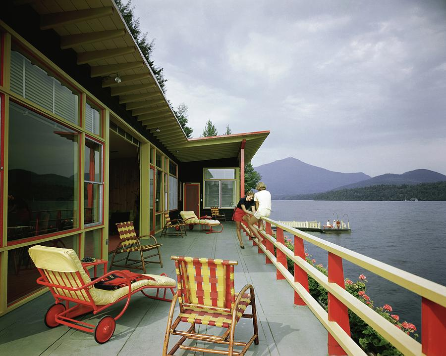 Two Women On The Deck Of A House On A Lake Photograph by Robert M. Damora