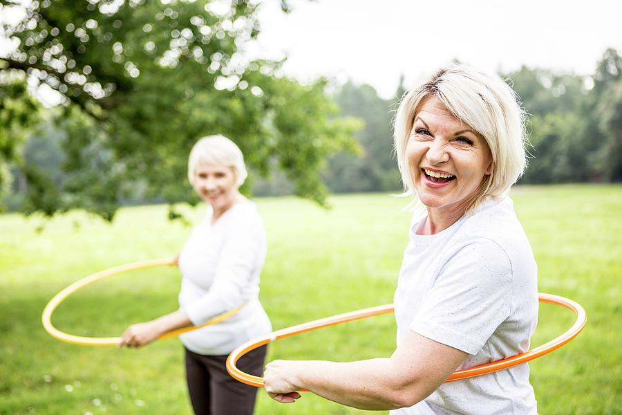 Two People Photograph - Two Women With Plastic Hoops by Science Photo Library