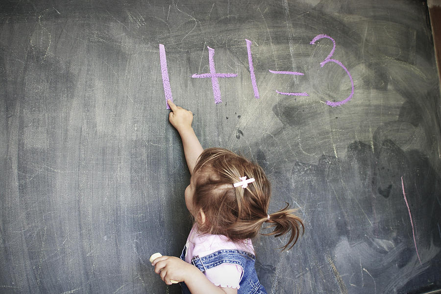 Two year old girl pointing at a blackboard Photograph by Geri Lavrov