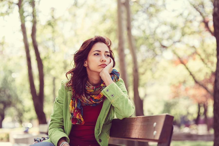 Unhappy Girl Sitting At Bench Photograph by Martin Dimitrov