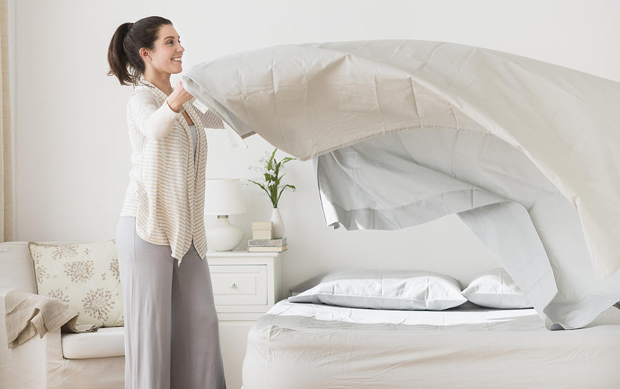 USA, New Jersey, Jersey City, Woman spreading sheet on bed Photograph by Tetra Images