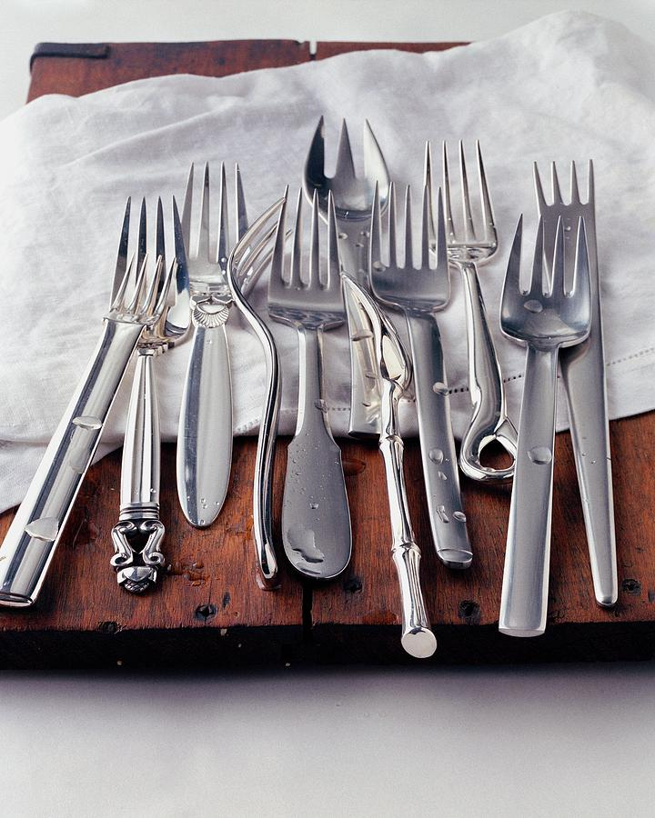 Various Forks On A Wooden Board Photograph by Romulo Yanes