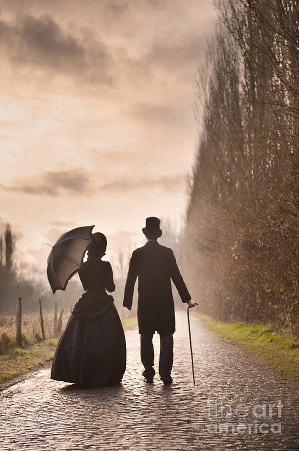 Victorian Man And Woman Walking On A Cobbled Avenue