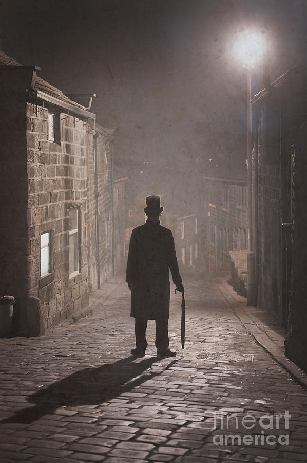 Victorian Man With Top Hat On A Cobbled Street At Night In