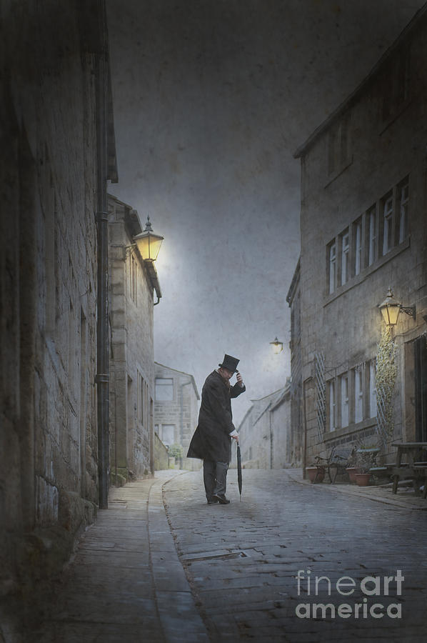 Victorian Man With Top Hat On A Cobbled Street At Night