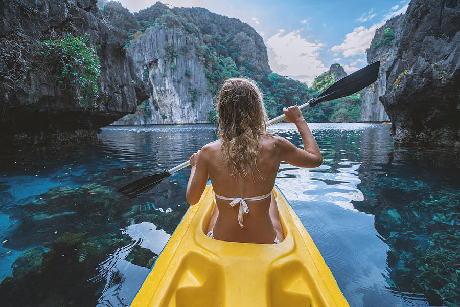 View Of A Young Woman Canoeing In Beautiful Tropical Lagoon Photograph by Swissmediavision