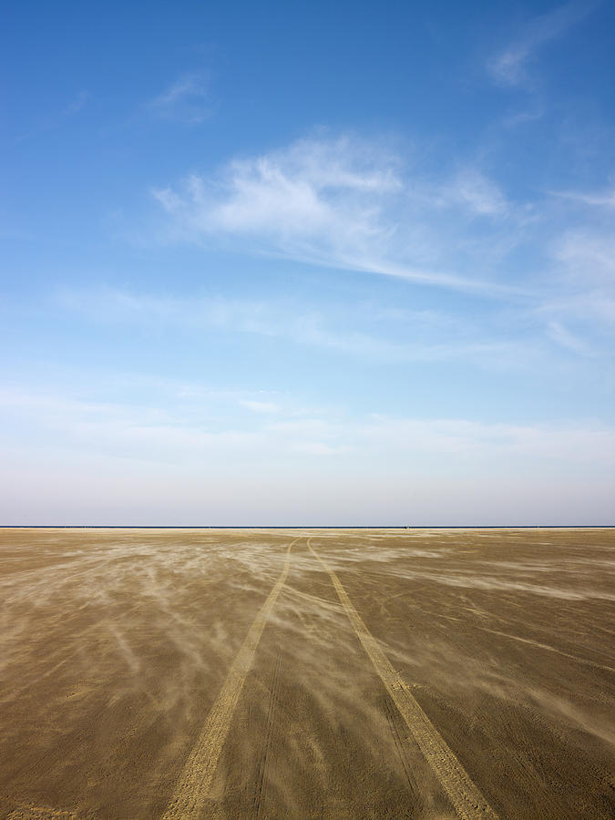 View Of Sandy Beach With Tire Tracks Photograph by Johner Images