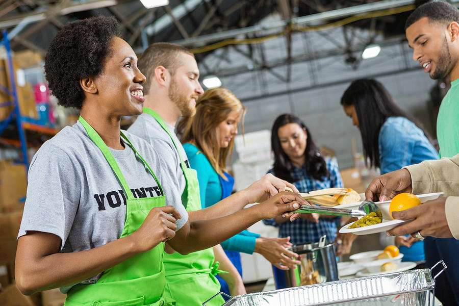 Volunteers serving healthy hot meal at soup kitchen Photograph by SDI Productions