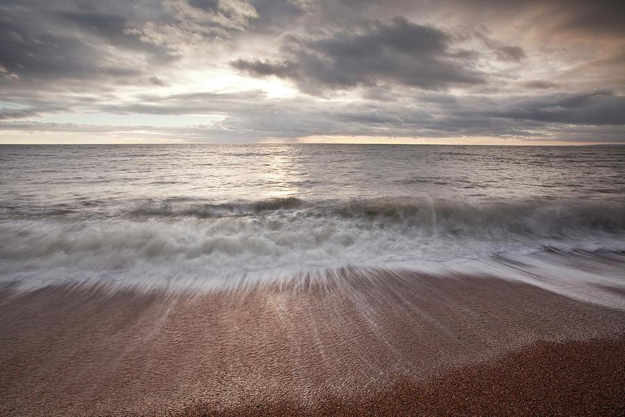 Waves Crashing Over The Beach At Burton Photograph by Julian Elliott Photography