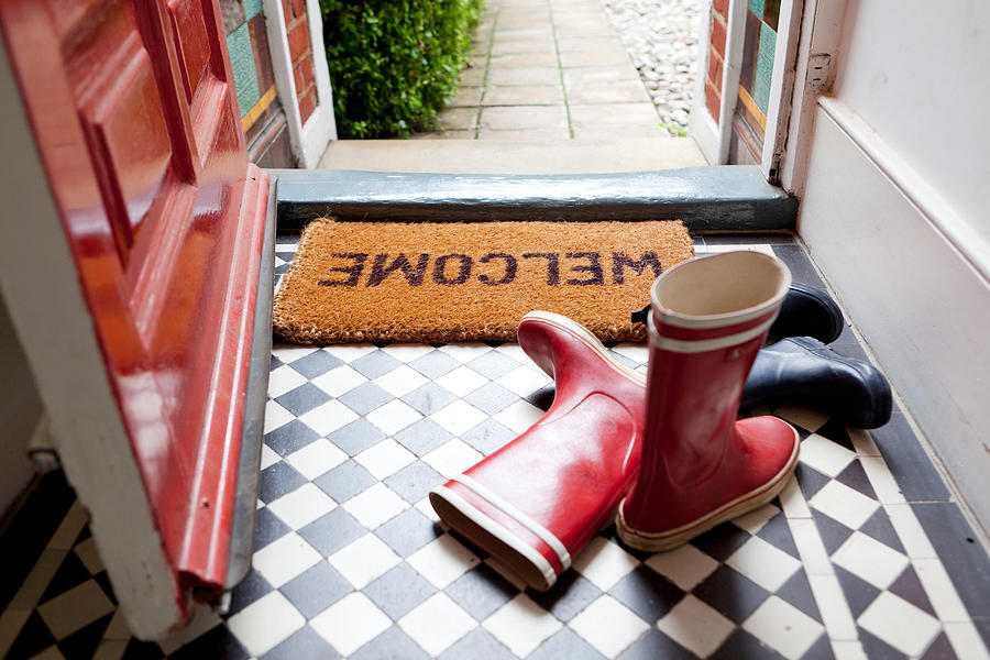 Welcome mat and wellington boots Photograph by Image Source