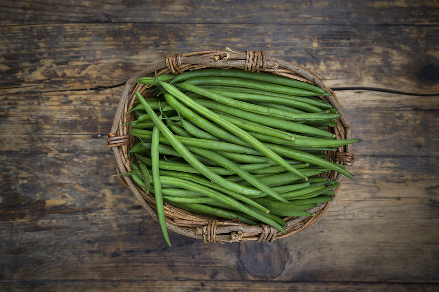 Wickerbasket Of Green Beans On Dark Wood Photograph by Westend61