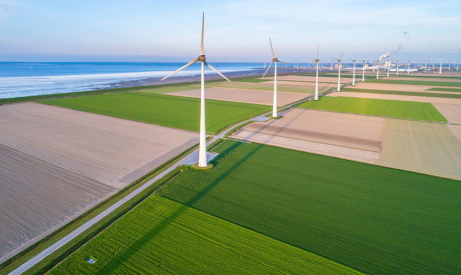 Wind turbines lined up along coast towards industrial area Photograph by Daniel Bosma