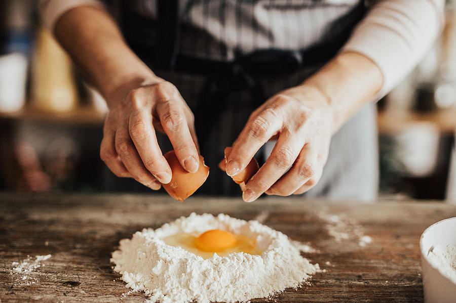 Woman adds an egg to the flour Photograph by Anchiy