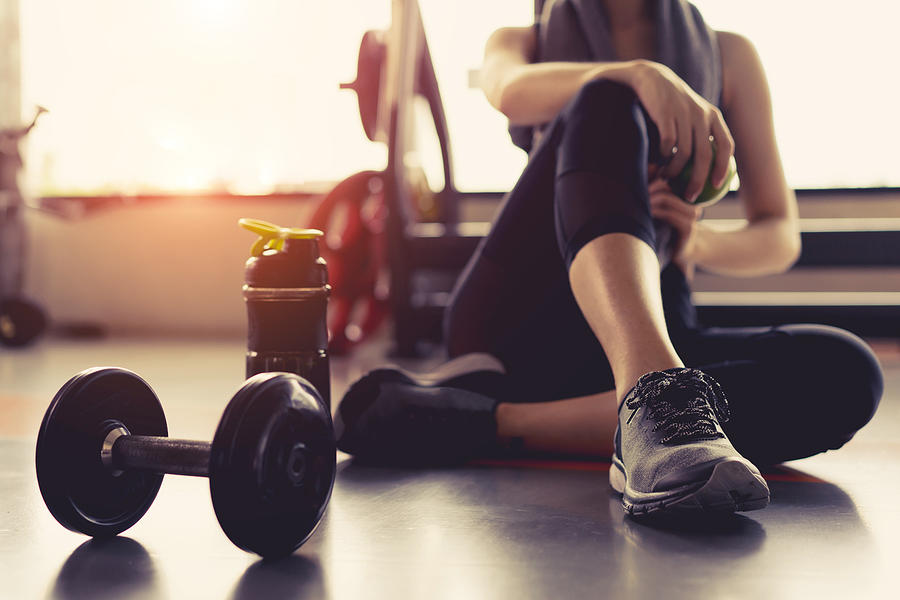 Woman exercise workout in gym fitness breaking relax holding apple fruit after training sport with dumbbell and protein shake bottle healthy lifestyle bodybuilding. Photograph by Champlifezy@gmail.com