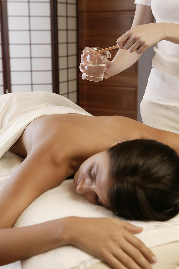 Woman getting hot oil massage Photograph by Comstock Images