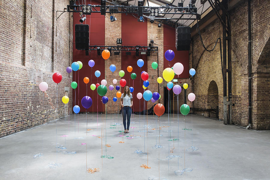 Woman in warehouse with colourful balloons Photograph by Anthony Harvie