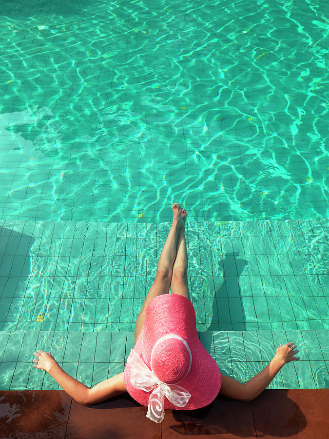 Woman Resting At Edge Of Swimming Pool Photograph by Johner Images