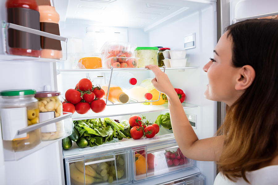 Woman Searching For Food In The Fridge Photograph by AndreyPopov
