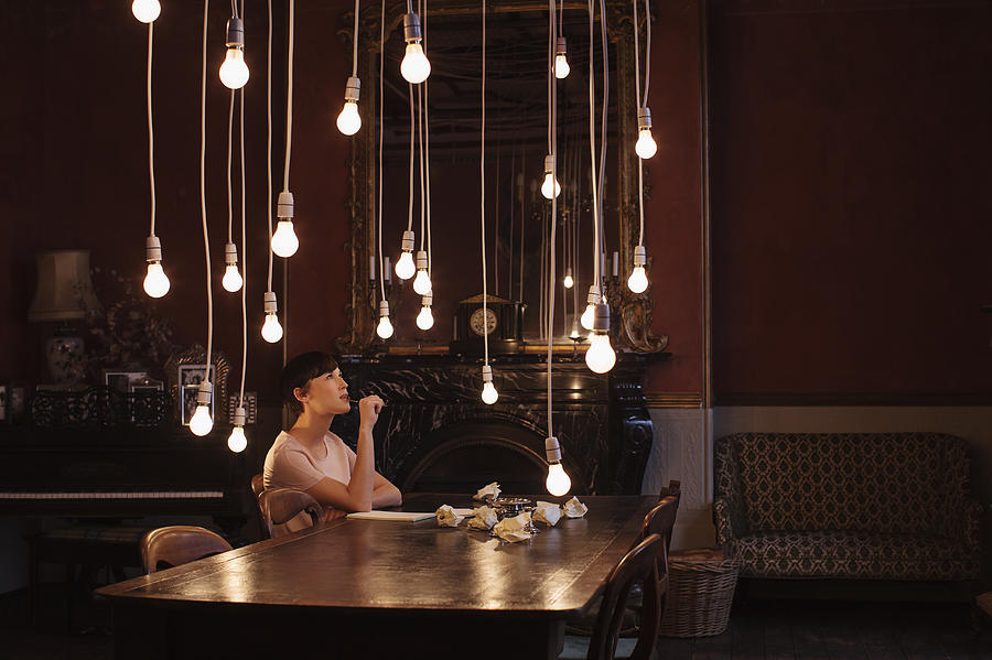 Woman sitting at table with hanging lightbulbs Photograph by Anthony Harvie