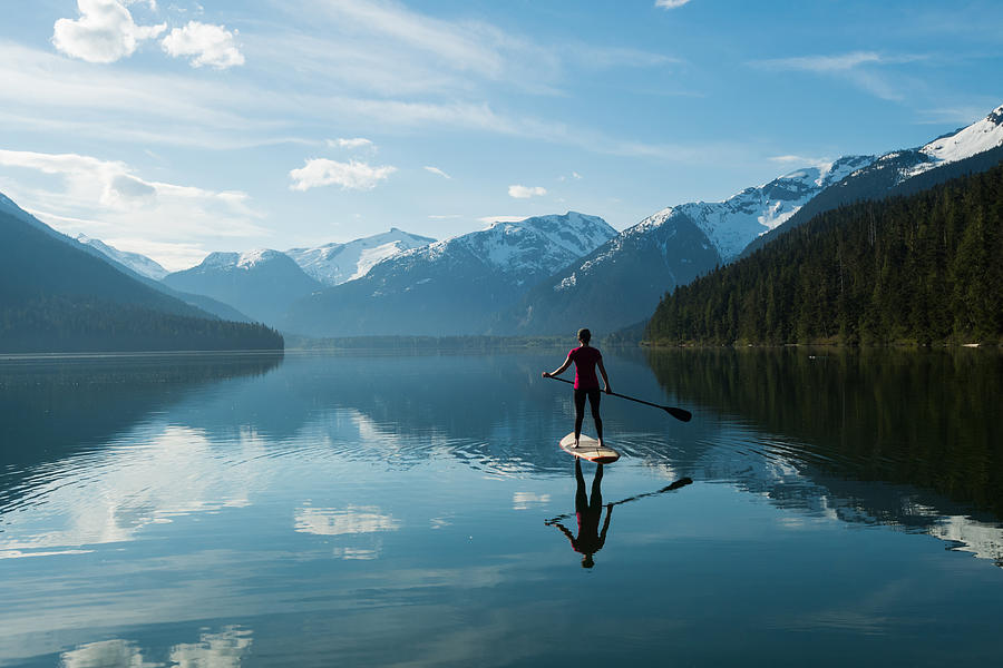 Woman stand up paddle boarding on a pristine mountain lake Photograph by stockstudioX