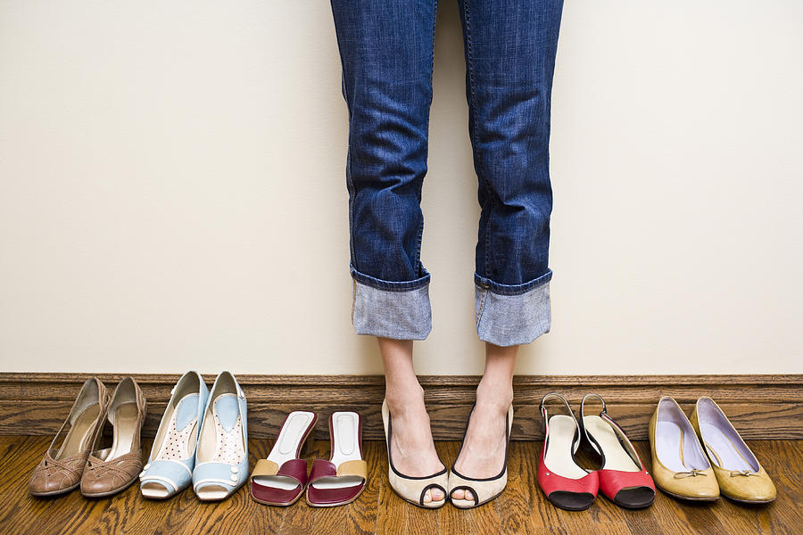 Woman Stands Wearing Heels With Her Collection Of Shoes Photograph by Michellegibson
