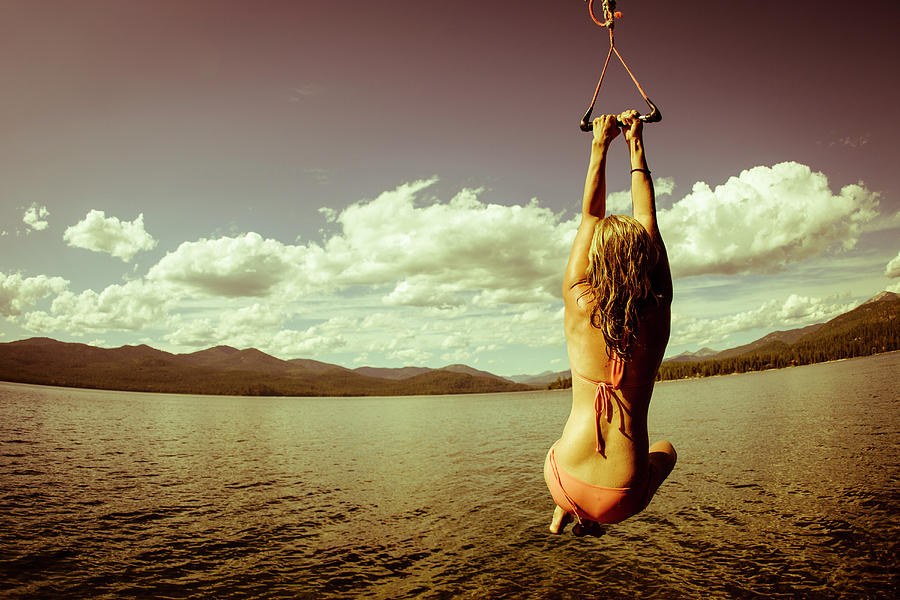 Woman Swinging On Rope Swing Over Lake Photograph By Gabe