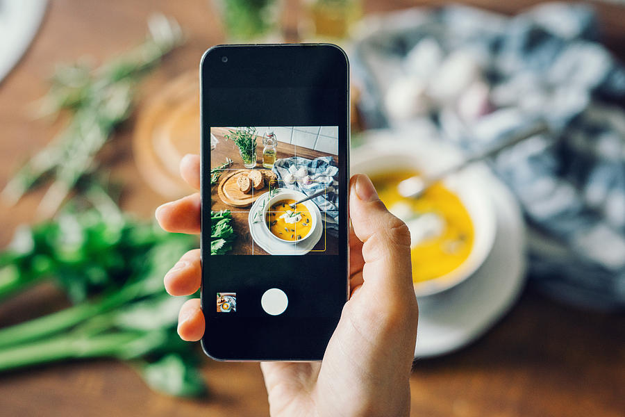 Woman taking photo of pumpkin soup with smartphone Photograph by Alexandra Iakovleva