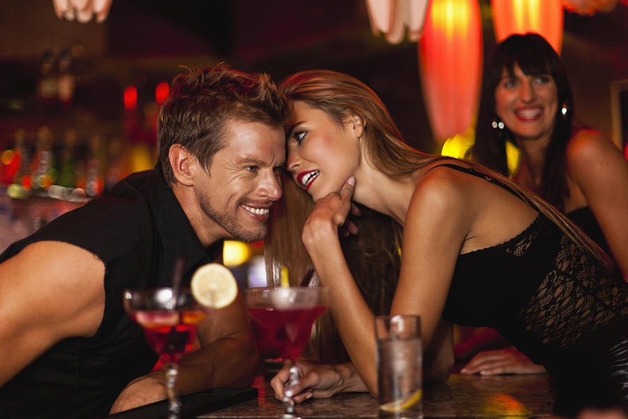 Woman Whispering To Bartender Photograph by Hybrid Images