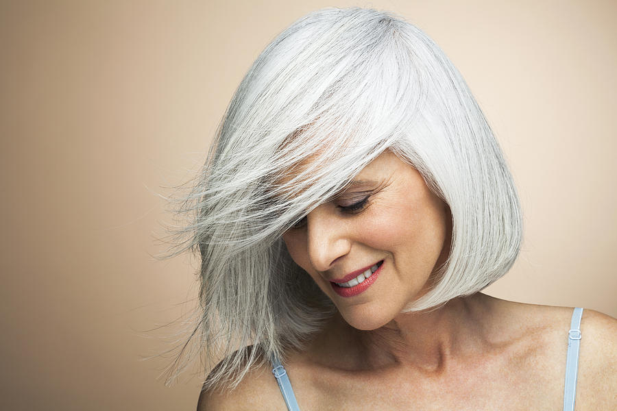 Woman With A Silvery,grey Bob Looking Down. Photograph by Andreas Kuehn