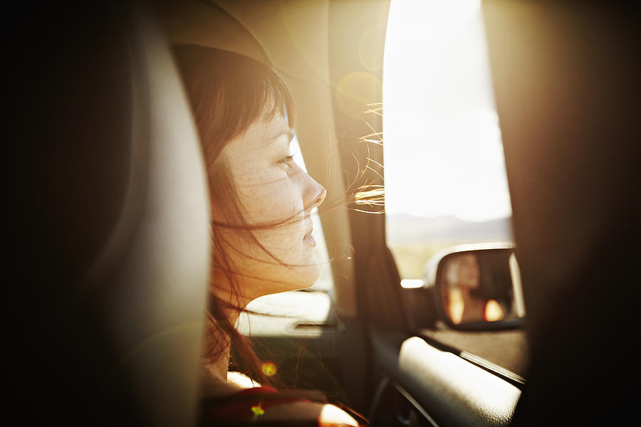 Woman With Hair Blowing Looking Out Window Of Car Photograph by Thomas Barwick