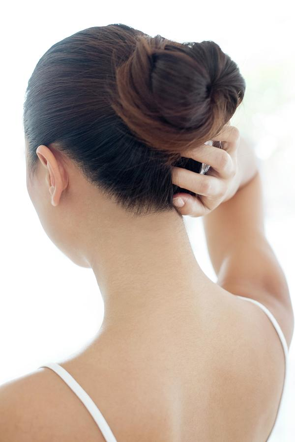 Indoors Photograph - Woman With Hair Bun Scratching Head by Science Photo Library