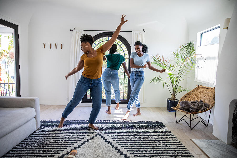 Women friends having fun at home dancing and singing in the living room Photograph by LeoPatrizi