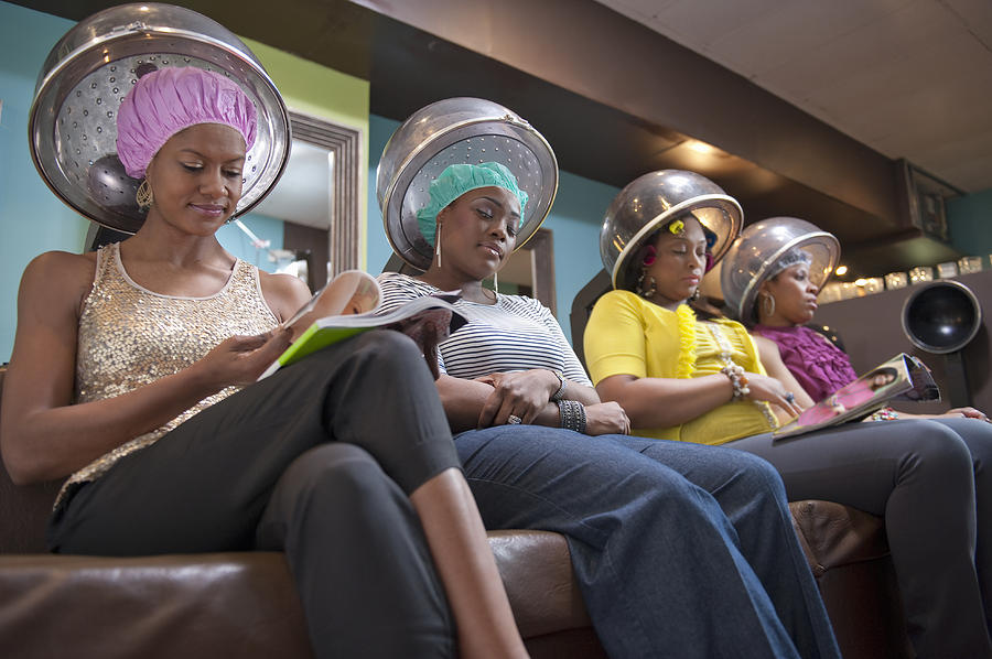 Women friends sitting under hair dryers at salon Photograph by Yellow Dog Productions