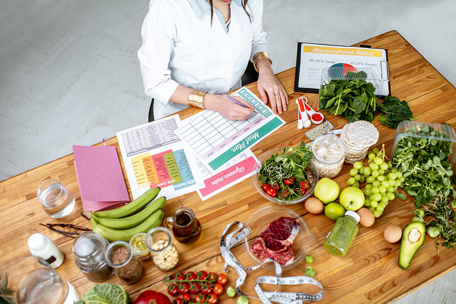 Writing a diet plan on the table full of healthy food Photograph by RossHelen