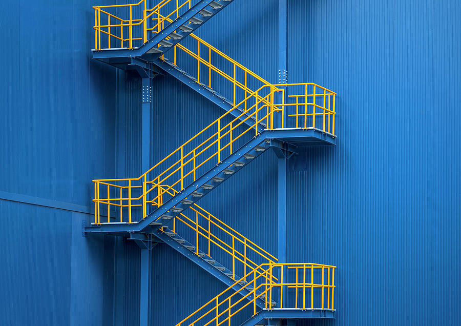 Yellow Metal Staircase Against A Blue Photograph by Ozgur Donmaz