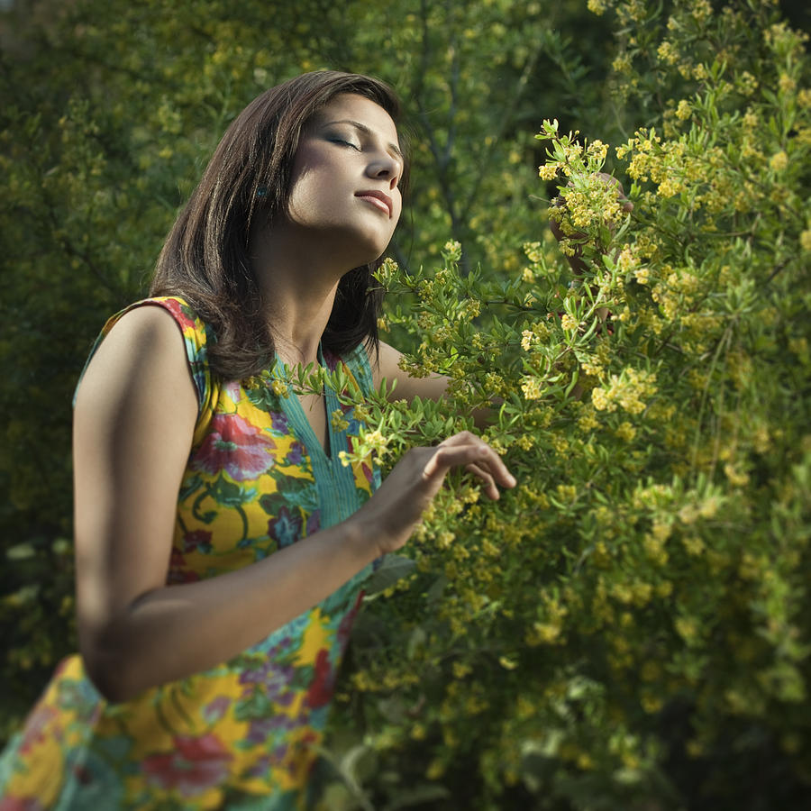 Young, beautiful Indian woman feeling fresh fragrance in blossoming nature. Photograph by Gawrav
