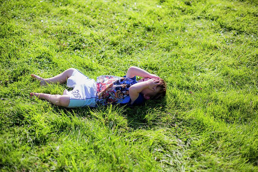 Child Photograph - Young Boy Lying On Grass by Samuel Ashfield