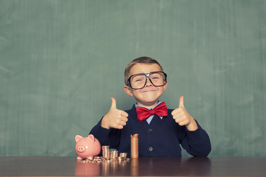 Young Boy Nerd Saves Money in His Piggy Bank Photograph by RichVintage