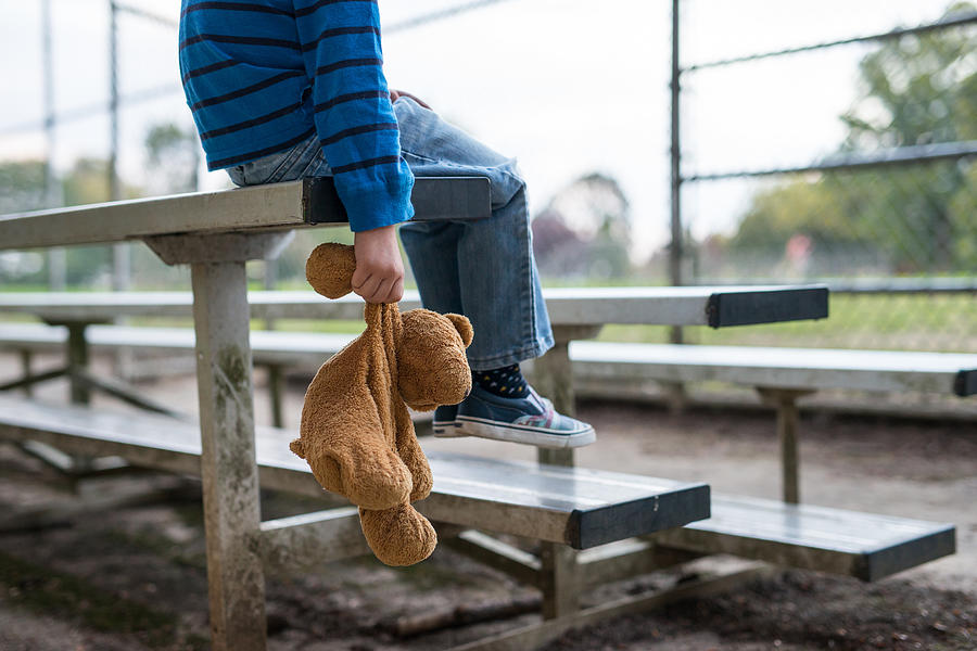 Young boy sitting by himself on on bleachers. Photograph by FatCamera