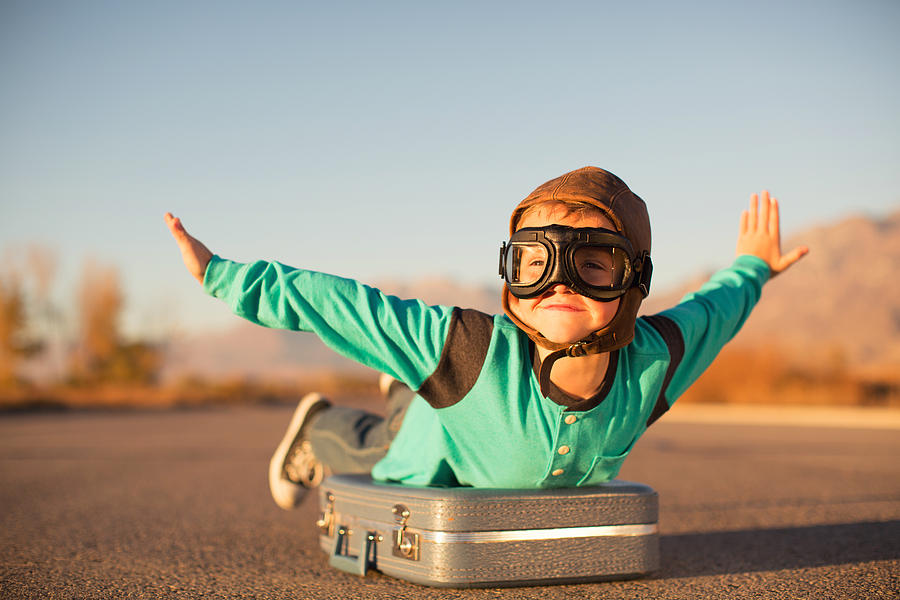 Young Boy with Goggles Imagines Flying on Suitcase Photograph by RichVintage