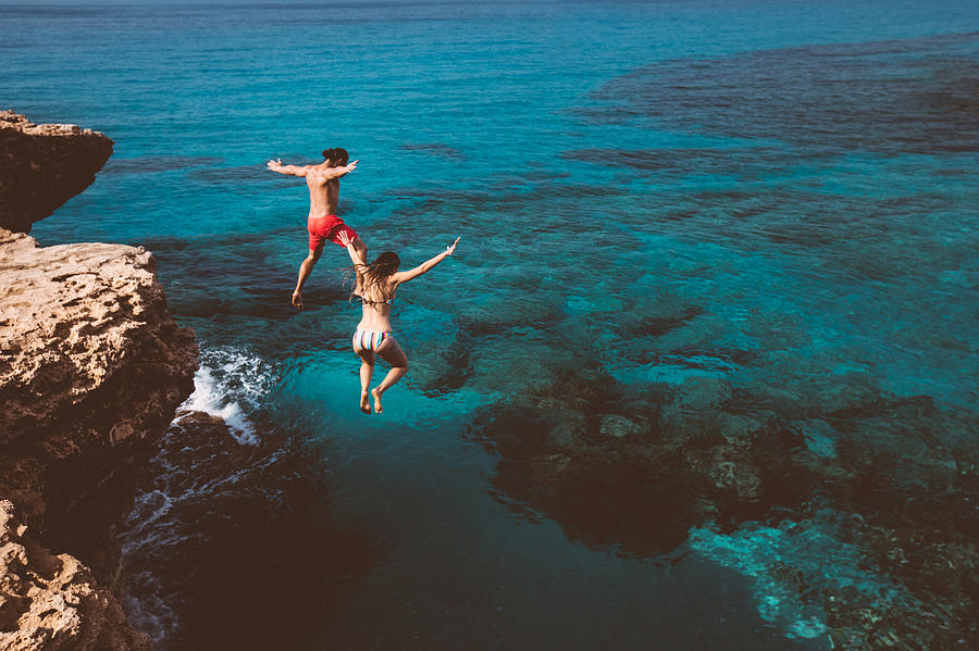 Young brave divers couple jumping off cliff into ocean Photograph by Wundervisuals